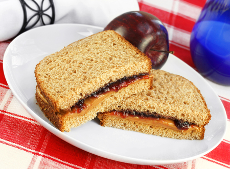 Healthy sandwich of peanut butter and grape jelly on whole wheat bread   Fresh apple and a glass of milk complete the lunch