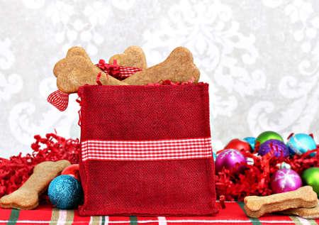 Homemade dog biscuits, shaped like bones, fill a festive Christmas bag   Healthy, homemade treats for a dog photo