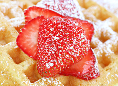 powdered sugar: Sliced and sugared strawberries on a waffle   Macro with selective focus