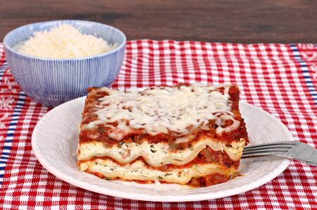 grated parmesan cheese: One slice of homemade lasagna with a side bowl of grated parmesan cheese.