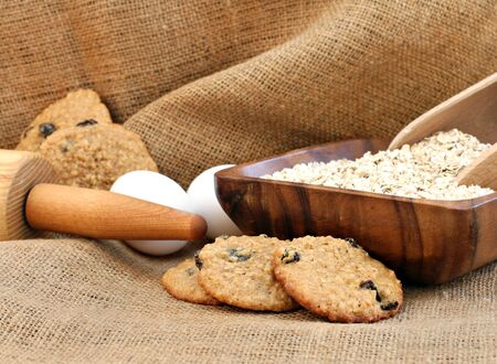 oats: Freshly baked oatmeal raisin cookies on burlap.  Oats, eggs and a rolling pin complete the image. Stock Photo