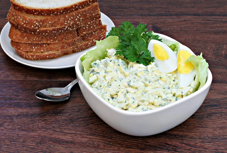 hard boiled: A bowl of fresh, homemade egg salad surrounded by lettuce and garnished with a hard boiled egg.
