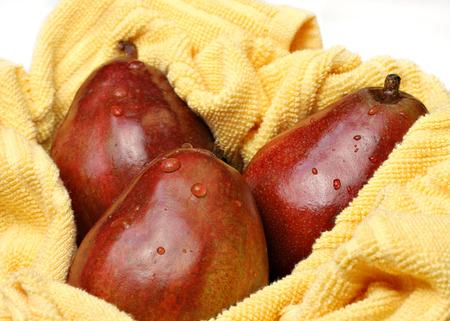 anjou: Tres, peras rojo Anjou saludables org�nicos en una toalla amarilla despu�s de ser lavado. Foto de archivo