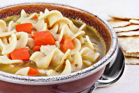 chicken noodle soup: A crock of hearty chicken noodle soup, close-up.  Crackers to the side.