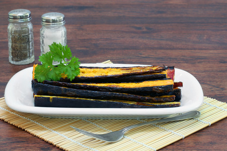 garnished: A stack of organic, healthy roasted purple carrots on a serving dish and garnished with parsley.
