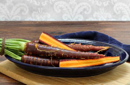 ?  ? carrot: Raw, se lava las zanahorias moradas en un plato ovalado. Zanahorias enteras y en rodajas para mostrar detalles. Foto de archivo