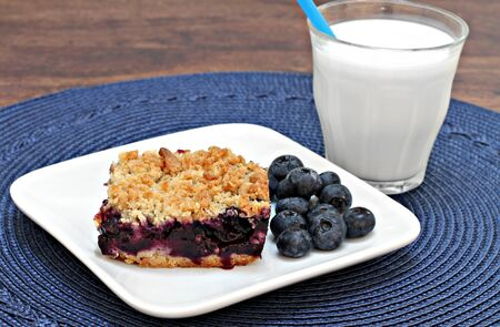 blueberries: One blueberry cookie bar with a streusel topping and a glass of milk.