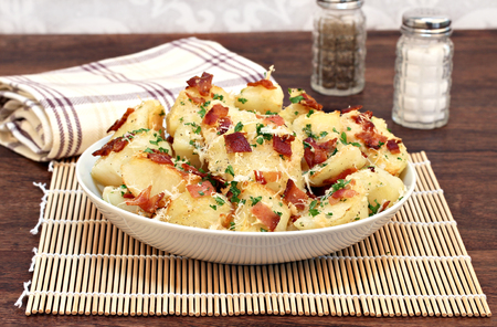 garnished: A bowl of roasted garlic, bacon and parmesan potatoes garnished with parsley bits. Stock Photo