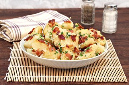 bacon bits: A bowl of roasted garlic, bacon and parmesan potatoes garnished with parsley bits. Stock Photo