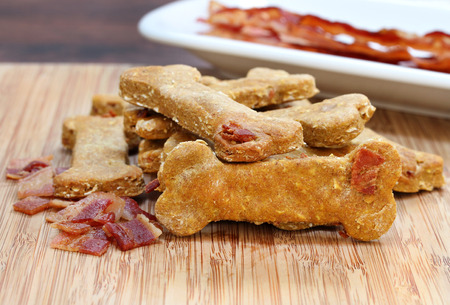 Pumpkin, bacon dog biscuits on a cutting board.  A homemade and healthy treat for your dog. Reklamní fotografie