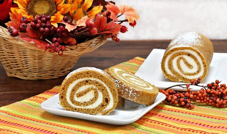 cream cheese: Pumpkin roll cake, whole and sliced, in a fall setting. Stock Photo