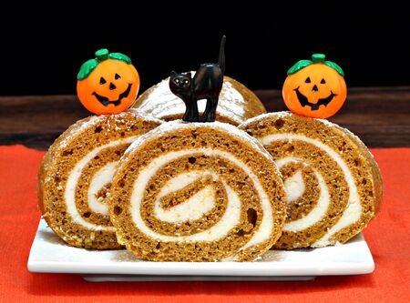 cream cheese: Pumpkin roll cake decorated with pumpkins and a black cat for Halloween.