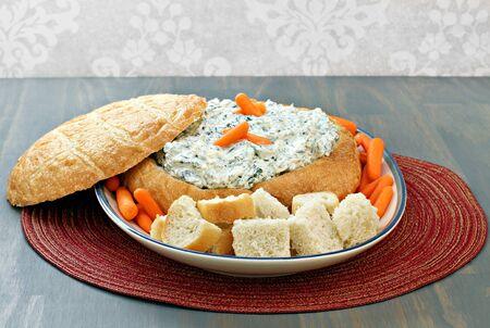 espinacas: , Delicioso dip de espinacas frescas en un pan redondo con cubitos de pan y zanahorias para la inmersión.