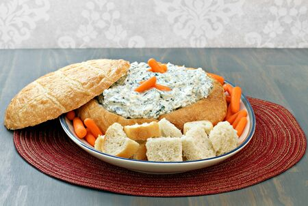 dips: Fresh, delicious spinach dip in a round loaf of bread with bread cubes and carrots for dipping.