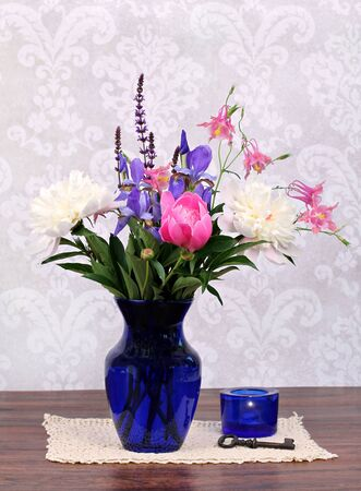 antique vase: An assortment of typical and beautiful spring flowers in a navy vase with candle and antique key to the side.Arrangement on an antique doily.