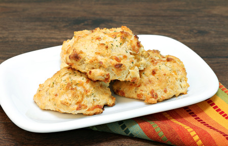 Three stacked cheddar, parsley and garlic biscuits.