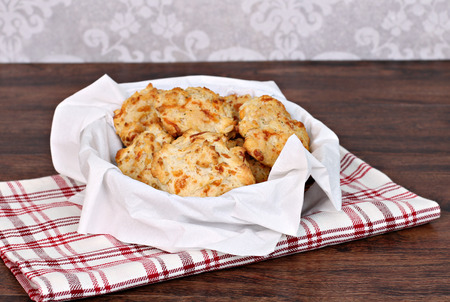 Fresh baked cheddar, garlic biscuits in a napkin lined basket.  Selective focus on front biscuit.