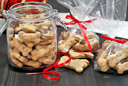 Homemade dog bones being packaged into cellophane bags as healthy gifts for dogs.  Selective focus on foreground cookies. Stockfoto