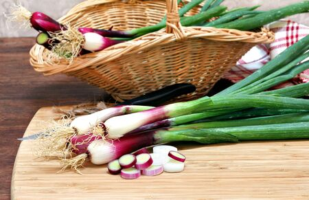 close up of onions in a basket: Spring onions, cebollitas cambray, both in a basket and on a cutting board being prepared for use. Stock Photo