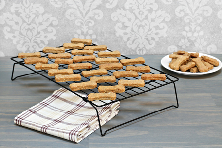 dog treat: Healthy, homemade dog cookies cooling on a wire rack.  Selective focus on foreground cookies with copy space. Stock Photo