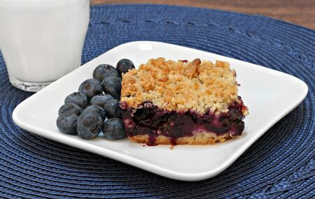 side bar: One blueberry bar cookie with streusel topping and a glass of milk.  Fresh organic blueberries on the side.