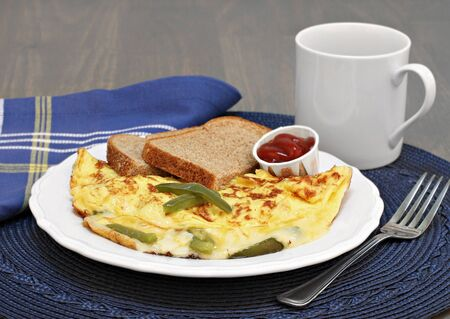 whole wheat toast: An egg, green bell pepper and cheese omelet with whole wheat toast and a side of ketchup. Stock Photo