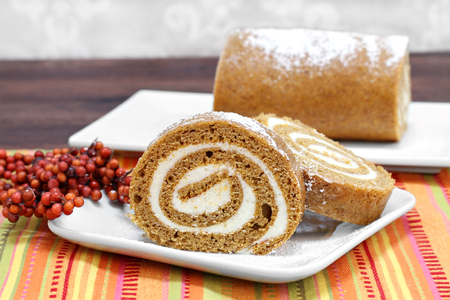 dynia: Sliced pumpkin roll cake with whole cake in background.  Fall setting and colors with copy space.