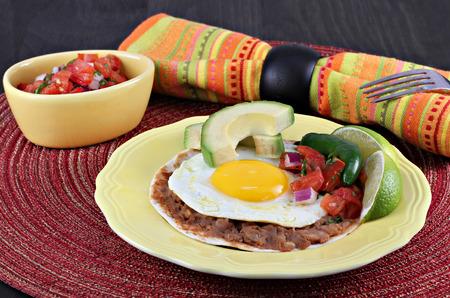 de focus: Tex Mex Huevos Rancheros, with pico de gallo, sliced avocado on a tortilla with refried beans.