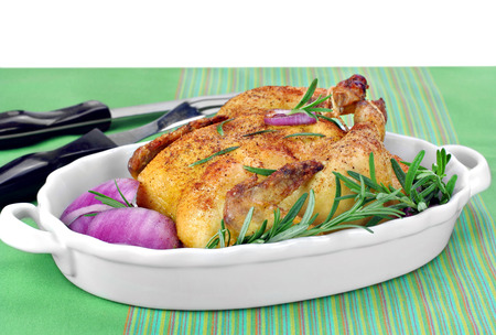 cornish: Roast chicken hen with fresh Rosemary and red onions for garnish.  Copy space. Stock Photo