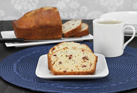 pound cake: Cranberry pound cake, slices on a plate and whole one in background with a mug of hot coffee.