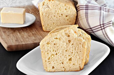 cheddar: Slices of cheddar cheese bread in front of loaf and a piece of cheddar. Stock Photo