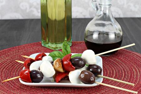 pimientos: Antipasto en un pincho. Pinchos incluyen aceitunas italianas, pimientos asados ??y ajo con queso mozzarella. Foto de archivo