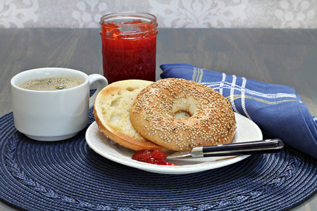 buttered: One toasted and buttered sesame bagel with homemade strawberry jam. Stock Photo
