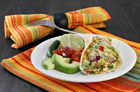 tex mex: Mexican breakfast of a breakfast taco with eggs and chorizo.  Sides of pico de gallo, avocado, lime and jalapeno. Stock Photo