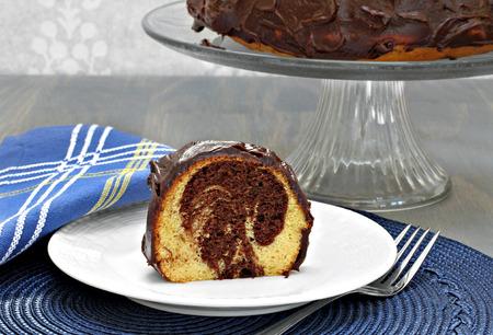 pastel de chocolate: Un trozo de chocolate de mármol y pastel de vainilla con el chocolate frente delante de un soporte de la torta con la torta entera.