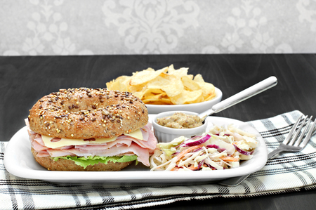 multi grain sandwich: A ham and swiss cheese sandwich on a whole grain multi seed bagel. Sides of spicy mustard, cole slaw and chips.  Copy space.
