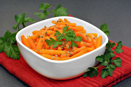 carrots: Healthy, organic baby carrots in a bowl garnished with parsley.
