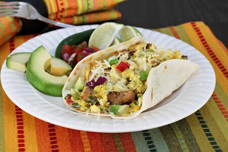 wraps: Huevos revueltos con chorizo, pimientos, cebolla y queso en una tortilla. Lados de aguacate, pico de gallo, lima y jalapeño.