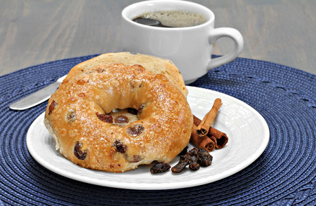One cinnamon raisin bagel buttered and toasted with a side of coffee.