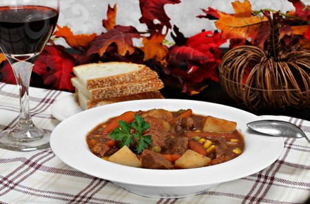 beef stew: A bowl of homemade beef stew, and a glass of wine in a fall table setting.