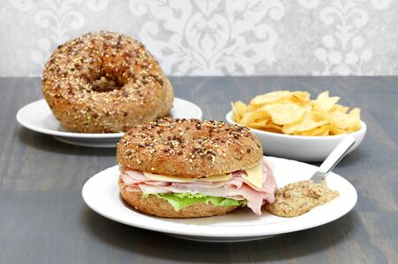 multi grain sandwich: Ham, swiss cheese and lettuce sandwich on a multi grain and seed bagel with a side of spicy mustard.