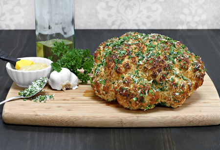 cooked: One whole head of roasted cauliflower on cutting board with roasting ingredients.