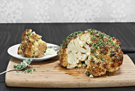 head of cauliflower: One whole roasted cauliflower head with a slice removed revealing inside appearance.