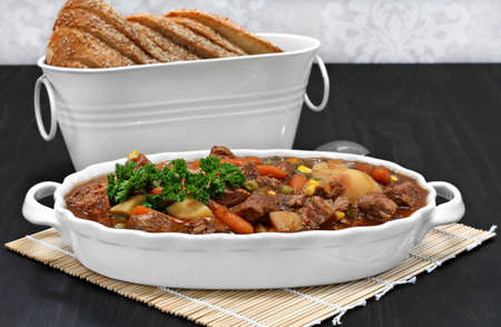 Homemade, healthy beef stew in an oval white casserole.  Italian bread as a side.