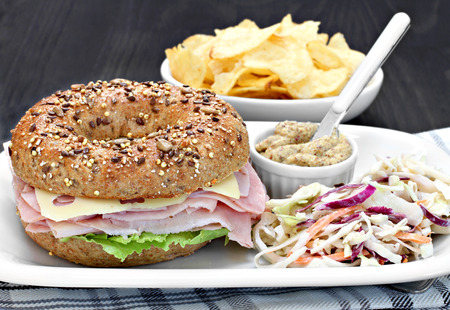 potato chips: A whole wheat bagel sandwich of ham, swiss cheese and mayo with a side of spicy mustard and cole slaw salad.