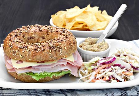 bocadillo: Todo un bocadillo de bagel de trigo de jamón, queso suizo y mayonesa con un poco de mostaza picante y ensalada de repollo cole. Foto de archivo