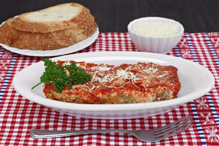 One slice of eggplant parmigiana garnished with parsley and a side of Italian bread. Banque d'images