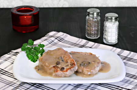 Two baked pork chops with mushroom gravy.