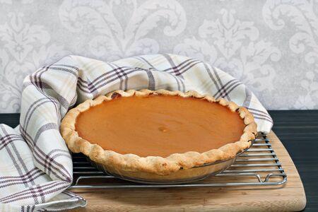 pumpkin pie: Homemade pumpkin pie, cooling with towel wrap.