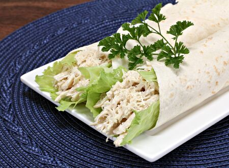 Two chicken caesar wraps with shredded chicken, lettuce and parmesan cheese garnished with parsley.  Close up, partial view. Stock Photo